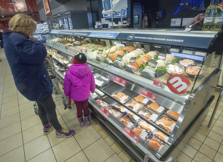 Une femme et une fillette regardent un comptoir de fruits de mer dans une épicerie grande surface